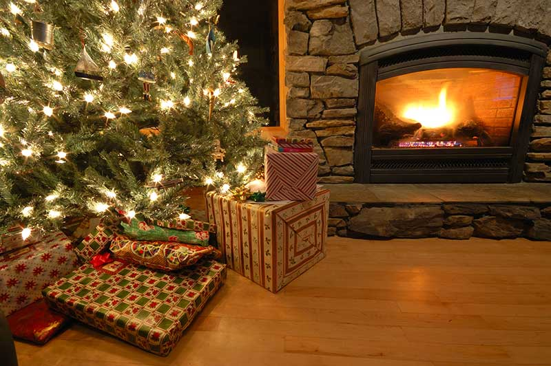 presents under a Christmas tree next to a fireplace