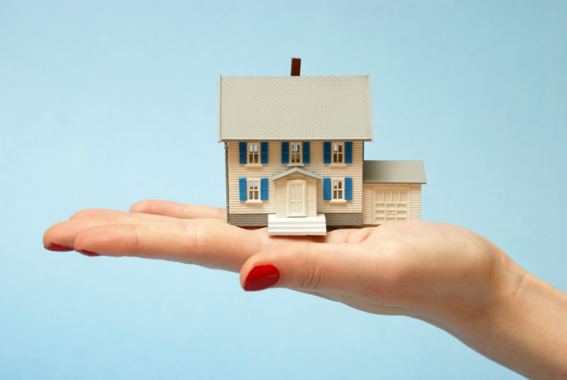 woman holds tiny house in her hand